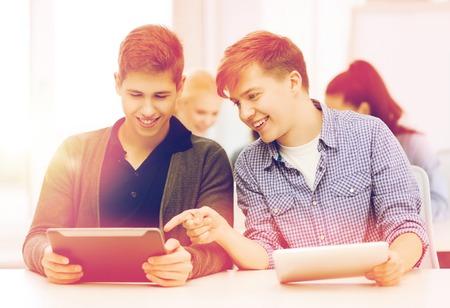 vzdělání, technologie a internet - dva usmívající se studenti při pohledu na tablet PC na přednáškách ve škole Reklamní fotografie