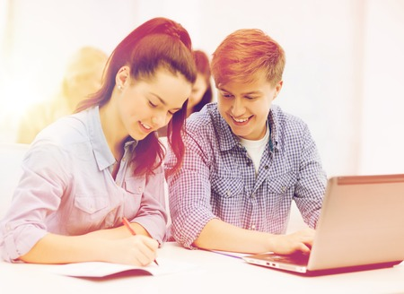 internet school: education, technology and internet concept - two smiling students with laptop and notebooks at school Stock Photo