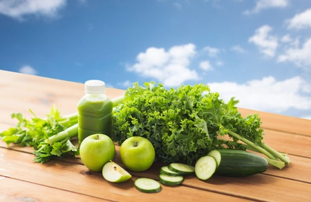 jugo verde: healthy eating, food, dieting and vegetarian concept - bottle with green juice, fruits and vegetables on wooden table over blue sky background Foto de archivo