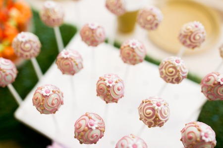 food, sweets, junk-food, holidays and celebration concept - close up of cake pops or lollipops on party table
