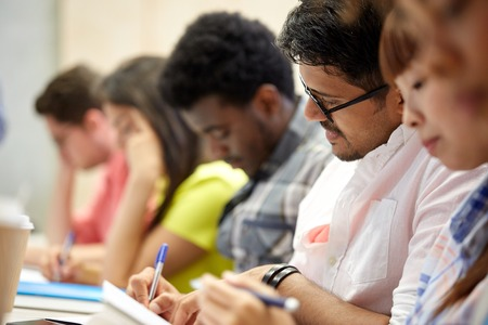 Bildung, Gymnasium, Hochschule, Lernen und Menschen Konzept - Gruppe von internationalen Studenten schriftlich bei Vortrag Standard-Bild