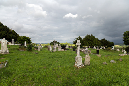 headstones: ancient monument and burial concept - old headstones and ruins on celtic cemetery graveyard in ireland