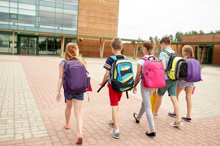 主な教育、友情、幼年期および人々 コンセプト - 野外を歩いている後ろからバックパックで幸せな小学生のグループ 写真素材 - 64634364