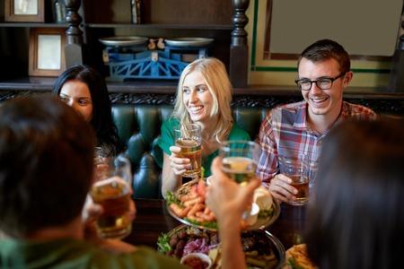 レジャー、食べ物や飲み物を食べる人々 し、コンセプト - 夕食、レストランやパブでビールを飲むと友達に笑顔の休日