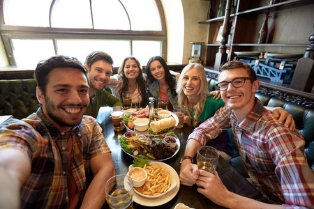 dinner food: people, leisure, friendship and technology concept - happy friends taking selfie, drinking beer and eating snacks at bar or pub Stock Photo