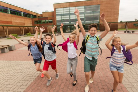 primary education, friendship, childhood and people concept - group of happy elementary school students with backpacks running and waving hands outdoors