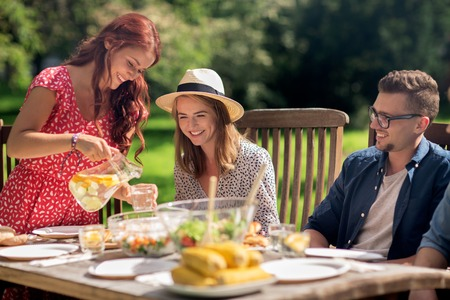 eating in the garden: leisure, holidays, eating, people and food concept - happy friends having dinner at summer garden party