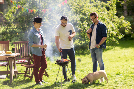 people   lifestyle: leisure, food, people, friendship and holidays concept - happy friends cooking meat on barbecue grill and drinking beer at summer outdoor party Stock Photo