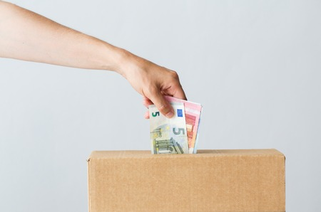 charity, finances, funding, investment and people concept - man putting euro money into donation box Stock Photo