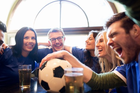 sport, people, leisure, friendship and entertainment concept - happy football fans or friends drinking beer and celebrating victory at bar or pub Stockfoto