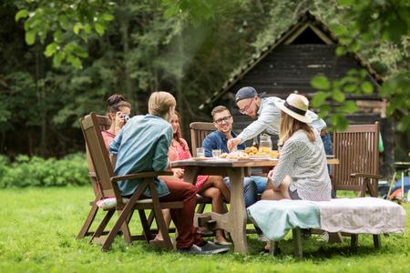 ocio, vacaciones, comer, la gente y el concepto de alimentos - amigos felices que cenan en fiesta en el jardín de verano