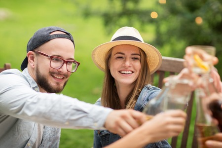 drinking alcohol: leisure, holidays, people, reunion and celebration concept - happy friends clinking glasses and celebrating at summer garden party Stock Photo