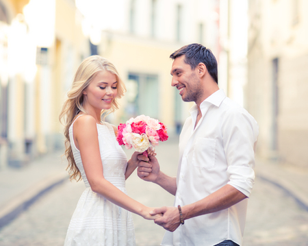 honeymoon: summer holidays, love, relationship and dating concept - couple with bouquet of flowers in the city