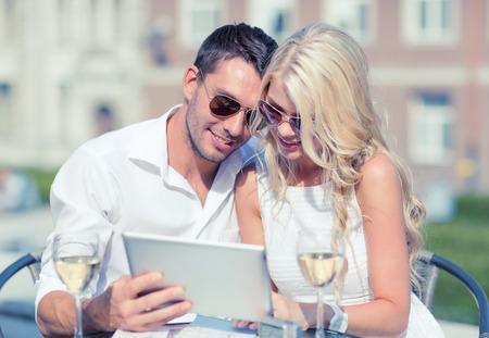夏の休日、デートや技術コンセプト - 都市のカフェでタブレット pc を探しているカップル