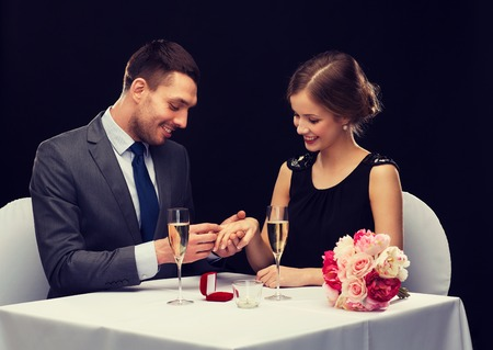 fingers put together: restaurant, couple and holiday concept - smiling man putting on finger engagement ring at restaurant