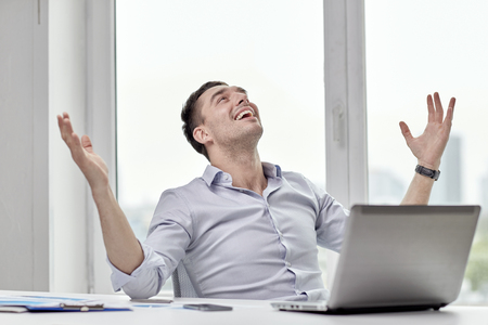 gladness: business, people, success and gladness concept - happy businessman with laptop in office Stock Photo