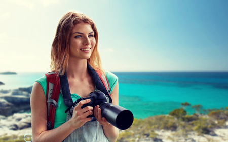 adventure, travel, tourism, hike and people concept - happy young woman with backpack and camera photographing over seashore or beach background Stock Photo