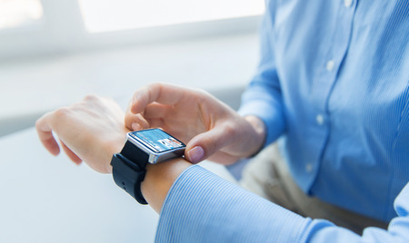 business, technology and people concept - close up of woman hands with news application on smart watch screen at office Stock Photo