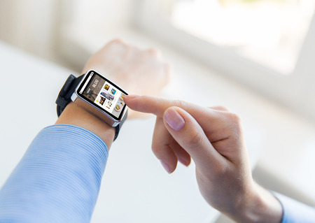 business, modern technology, blogging, media and people concept - close up of female hands setting smart watch with internet blog on screen at office Stock Photo