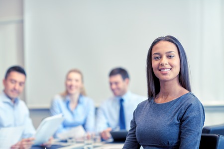 happy worker: business, people and teamwork concept - smiling businesswoman with group of businesspeople meeting in office