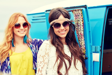 trip over: summer holidays, road trip, vacation, travel and people concept - smiling young hippie women over minivan car