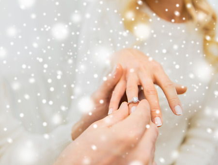 verlobt: love, couple, relationship and holidays concept - close up of man giving diamond ring to woman