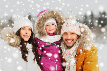 mujer hijos: la paternidad, la moda, la temporada y concepto de la gente - familia feliz con el niño en ropa de invierno al aire libre