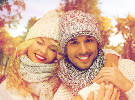 season, people, love and fashion concept - happy family couple in warm clothes over autumn background Stock Photo