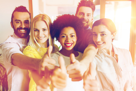 business, startup, people and teamwork concept - happy creative team showing thumbs up in office Stock Photo