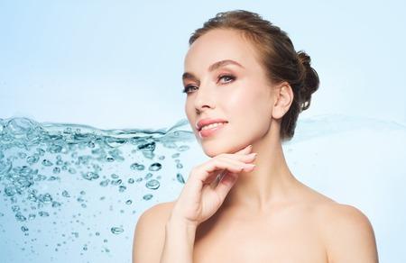 Schönheit, Menschen und Gesundheit Konzept - schöne junge Frau, die ihr Gesicht auf blauem Hintergrund mit Wasser spritzen zu berühren