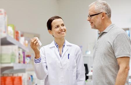 医学、薬学、医療、人々 コンセプト - ドラッグ ストアで年配の男性顧客に幸せな薬剤師表示薬物