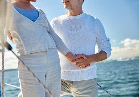 sailing, age, tourism, travel and people concept - close up of happy senior couple holding hands on sail boat or yacht deck floating in sea