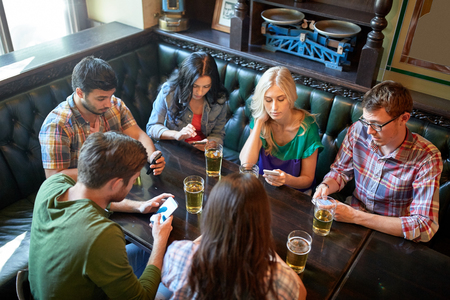pubs: people, leisure, friendship and communication concept - friends with smartphones drinking beer and texting at bar or pub Stock Photo