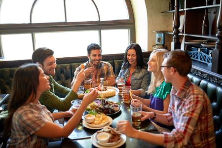 irish woman: leisure, eating, food and drinks, people and holidays concept - smiling friends having dinner and drinking beer at restaurant or pub