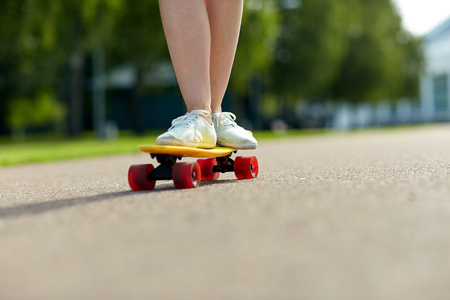 skateboarder: skateboarding, leisure, extreme sport and people concept - close up of teenage girl legs riding short modern cruiser skateboard on road