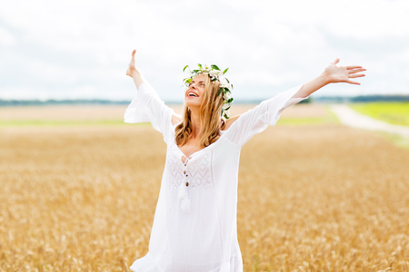 flowers sun: happiness, nature, summer holidays, vacation and people concept - smiling young woman in wreath of flowers and white dress on cereal field