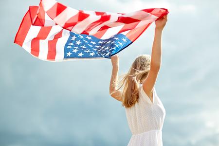 国、愛国心、独立記念日、人々 の概念 - 屋外でのアメリカ国旗の白ドレスで幸せな笑顔若い女