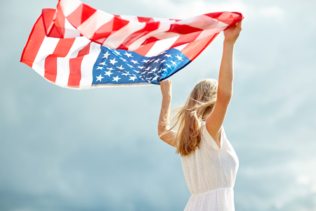 country, patriotism, independence day and people concept - happy smiling young woman in white dress with national american flag outdoors Standard-Bild