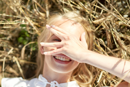 covering: nature, summer holidays, vacation and people concept - close up of happy young woman lying on cereal field and covering face by hand