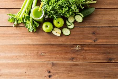 tomando jugo: alimentación saludable, la comida, la dieta y el concepto vegetariana - cerca de la botella con el jugo verde, frutas y verduras en la mesa de madera