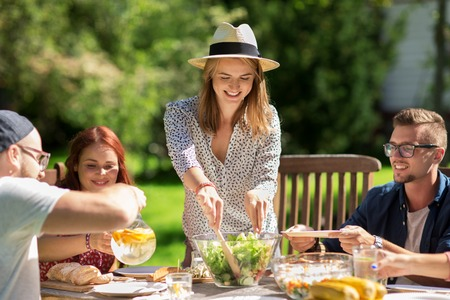 dinner food: leisure, holidays, eating, people and food concept - happy friends having dinner and sharing salad at summer garden party