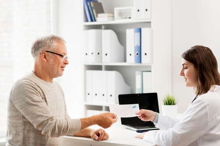 prescription medicine: medicine, age, health care and people concept - senior man and doctor with prescription meeting in medical office at hospital Stock Photo