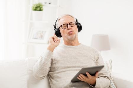 technologie, mensen, levensstijl en afstandsonderwijsconcept - gelukkige hogere mens met computer en hoofdtelefoons die van tabletpc aan muziek luisteren en thuis zingen