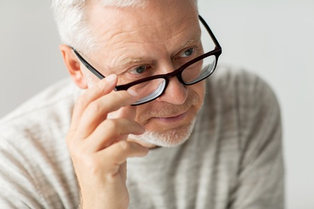 eyesight: old age, problem and people concept - close up of senior man in glasses thinking Stock Photo