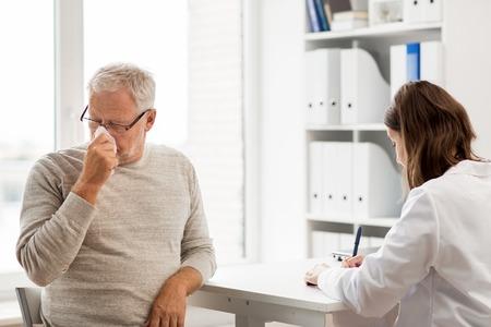 의학, 나이, 건강 관리, 독감 및 사람들이 개념 - 병원에서 의료 사무실에서 작성하는 클립 보드와 함께 냅킨과 의사와 코를 불고 수석 남자