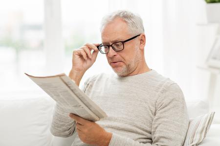 el ocio, la información, las personas, la visión y el concepto de medios de comunicación de masas - hombre mayor en los vidrios que lee el periódico en su casa Foto de archivo