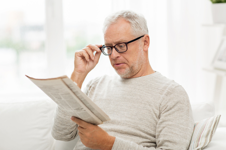 eyesight: leisure, information, people, vision and mass media concept - senior man in glasses reading newspaper at home