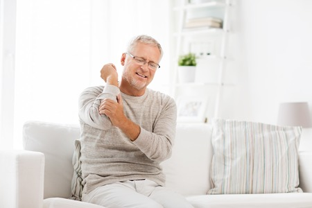 people, healthcare and problem concept - unhappy senior man suffering from elbow pain at home