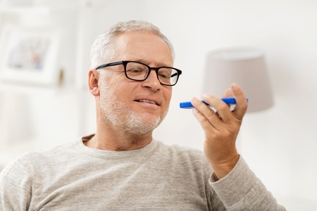 using voice: technology, people, lifestyle and communication concept - happy senior man using voice command recorder or calling on smartphone at home Stock Photo