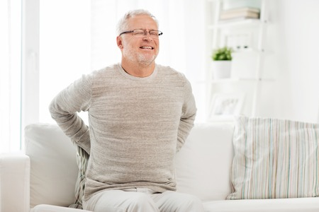 reins: people, healthcare and problem concept - unhappy senior man suffering from pain in back or reins at home Stock Photo